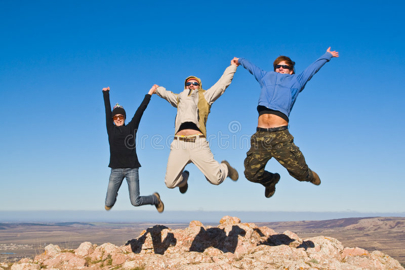 Group of hikers jumping on mountain summit. Three hikers jumping cheerfully on mountain summit in clear sunny weather royalty free stock photos