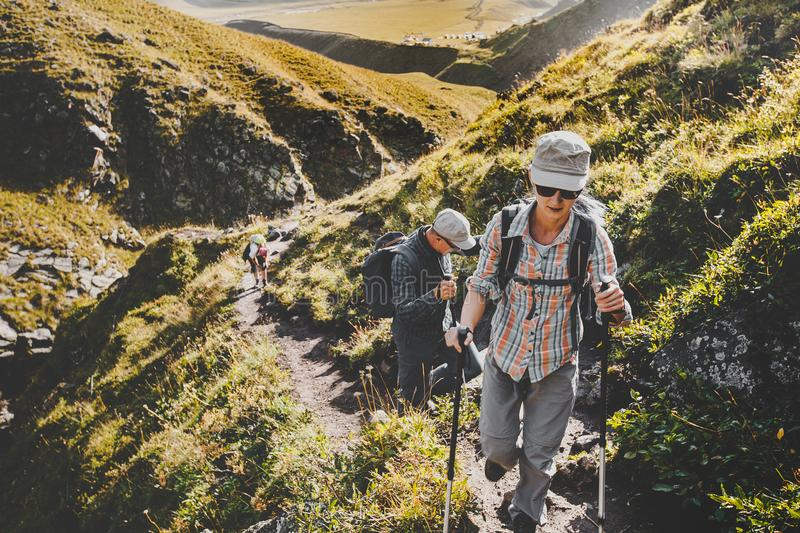 Group Of Hikers Walking Along In Summer Mountains, Journey Travel Trek Concept. Group Of Hikers Man And Womans With Trekking Poles Walking Along In Summer stock image