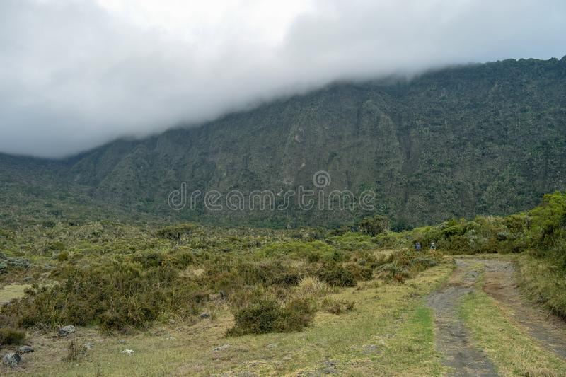 A group of hikers at Mount Meru, Tanzania. A hiker against a foggy mountain background at Mount Meru, Arusha National Park, Tanzania royalty free stock image