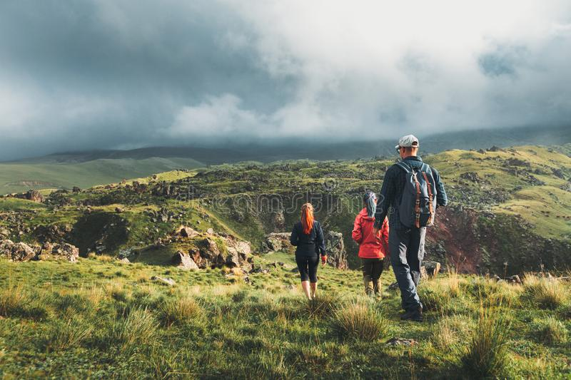 Group Of Hikers Walking Along The Green Hills, Rear View. Travel Tourism Discovery Concept. Group of backpackers, a men and two women walking along the green stock photo
