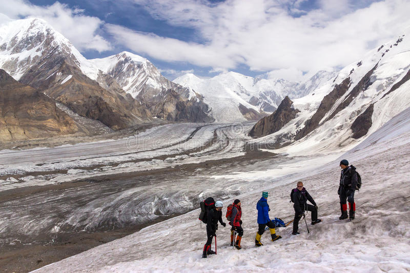 Group of Hikers Walking on Snow and Ice Terrain stock images