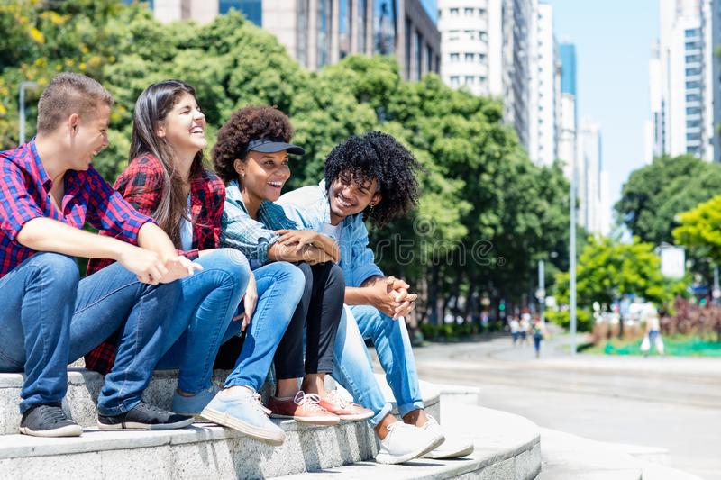 Group of hispanic and african american hipster young adults in the city. In the summer stock image