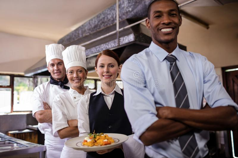 Group of hotel staffs standing with armas crossed in kitchen royalty free stock photography