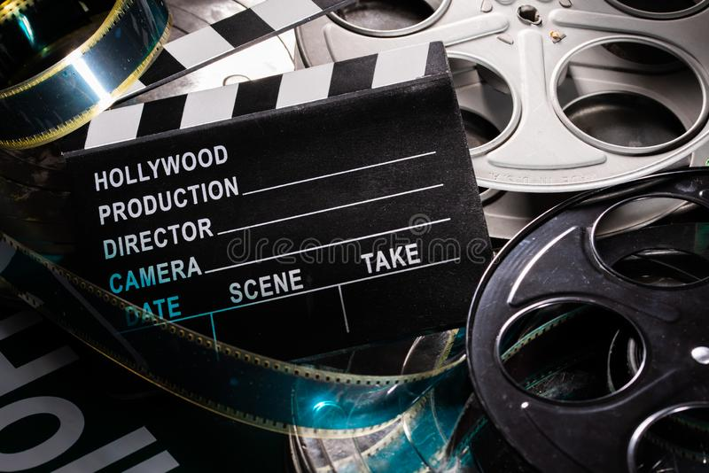 Movie clapper and film reel on a wooden background royalty free stock image