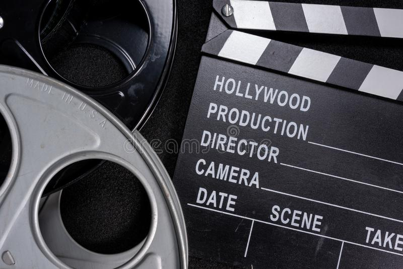 Movie clapper and film reel on a wooden background stock images