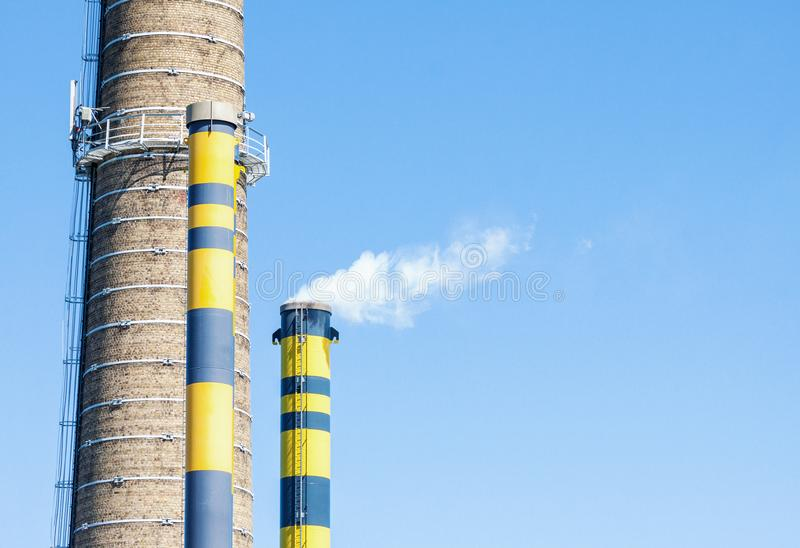 Group of industrial chimneys with smoke against blue sky stock photos