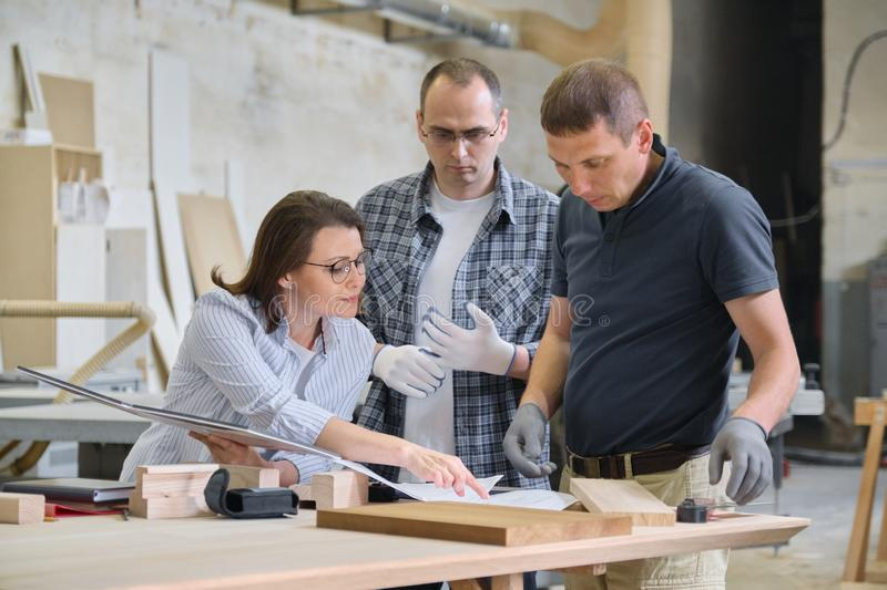 Group of industrial people client, designer or engineer and workers working together on project of wooden furniture stock photos