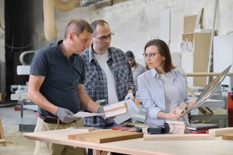 Group of industrial people client, designer or engineer and workers working together on project of wooden furniture. Teamwork in carpentry workshop royalty free stock image