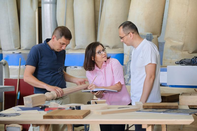 Group of industrial people working together, Teamwork in carpentry workshop. Group of industrial people client, designer or engineer and workers working together royalty free stock image