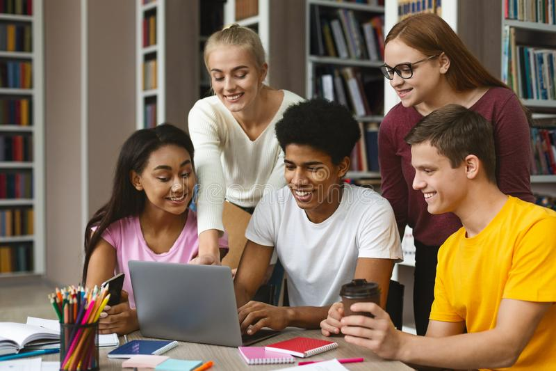 Group of international classmates checking on new project. Multinational Group Of College Classmates Checking On New Project, looking at laptop screen and royalty free stock photo