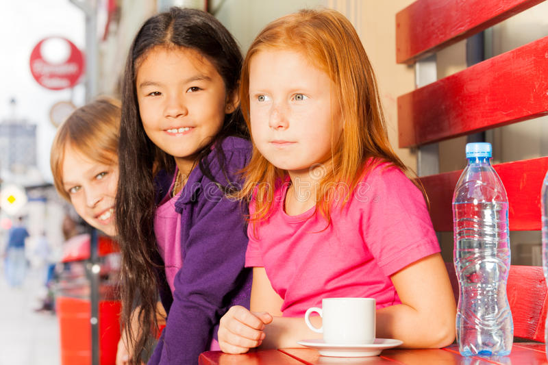 Group of international kids sit at cafe outside royalty free stock photography