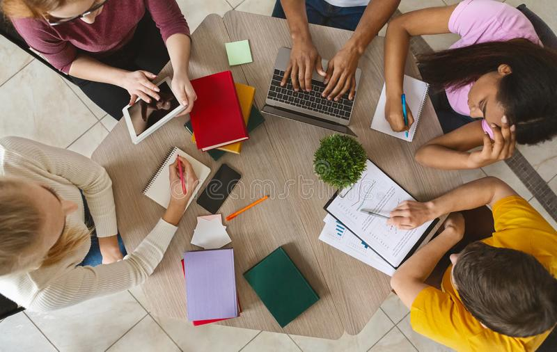 Group of international students sitting at table, top view. Education, high school, people and technology concept. Group of international students sitting at royalty free stock photography