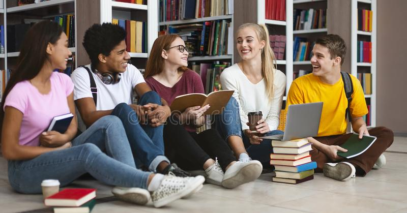 Group of international students talking over homework. Group of international students sitting on the floor next to bookshelves, talking over homework at library royalty free stock images