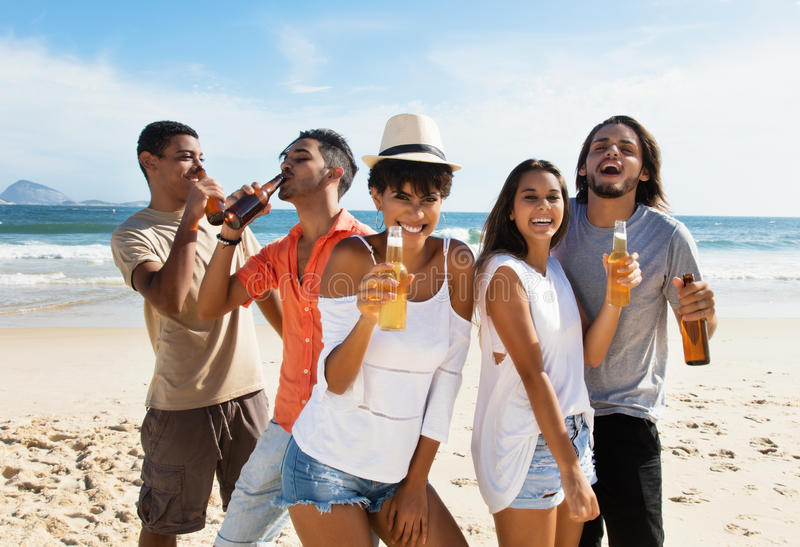 Group of international young adults celebrating at beach. Outdoor in the summer royalty free stock photography