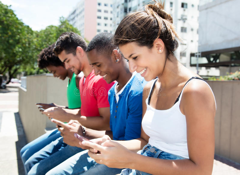 Group of international young adults typing message at phone. In city with buildings and green plants and trees in the background stock photography