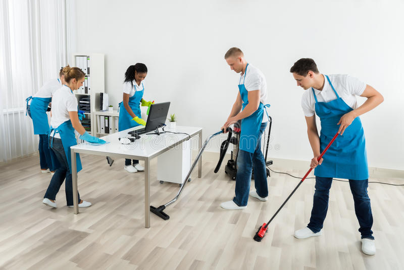 Group Of Janitors Cleaning The Office royalty free stock image