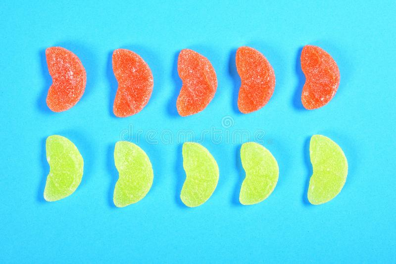 Group of jelly candies piece of orange fruit color yellow and orange on blue background royalty free stock photos
