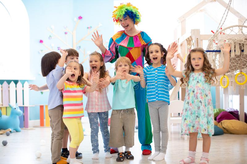 Group of joyful kids play with clown on birthday party stock photos