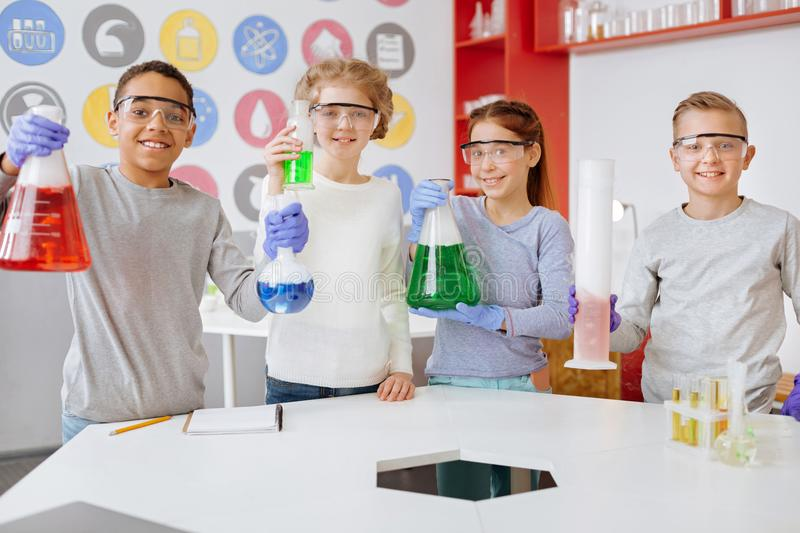 Group of joyful students posing with chemical flasks in lab royalty free stock photography
