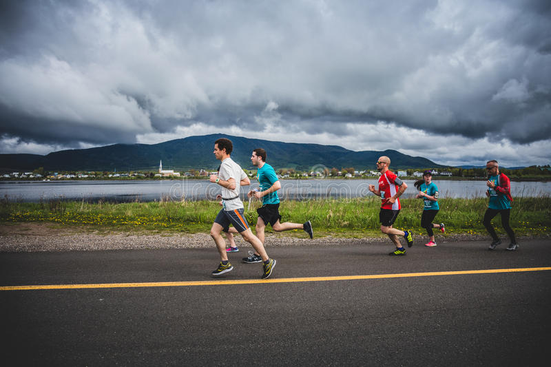 Group of 10K Runners in front of a beautiful Mountain Landscape. CARLETON, CANADA - June 4, 2017. During the 5th Marathon of Carleton in Quebec, Canada. Group of stock photo
