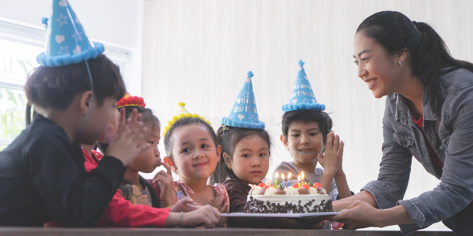 Group of kid friends waiting to blow birthday cake royalty free stock photo