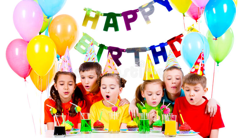 Group of kids blowing candles at the birthday party. Group of kids in colorful shirts blowing candles at the birthday party - isolated on a white royalty free stock image