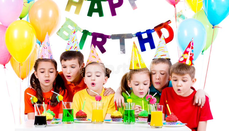 Group of kids blowing candles at the birthday party. Group of kids in colorful shirts blowing candles at the birthday party - isolated on a white stock photo