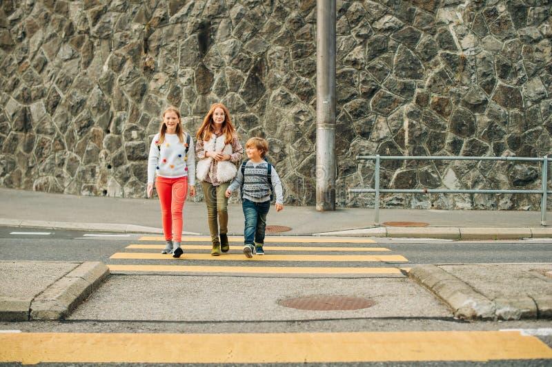 Group of 3 kids crossing the road, walking back to school. Wearing backpacks stock photo
