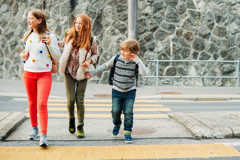 Group of 3 kids crossing the road, walking back to school. Wearing backpacks stock images