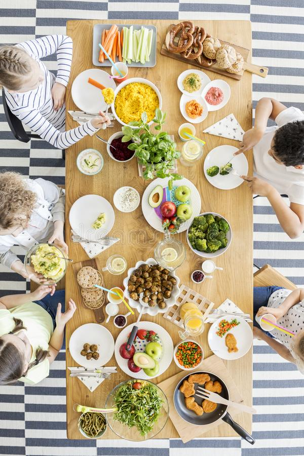 Group of kids eating healthy dinner with vegetables stock image