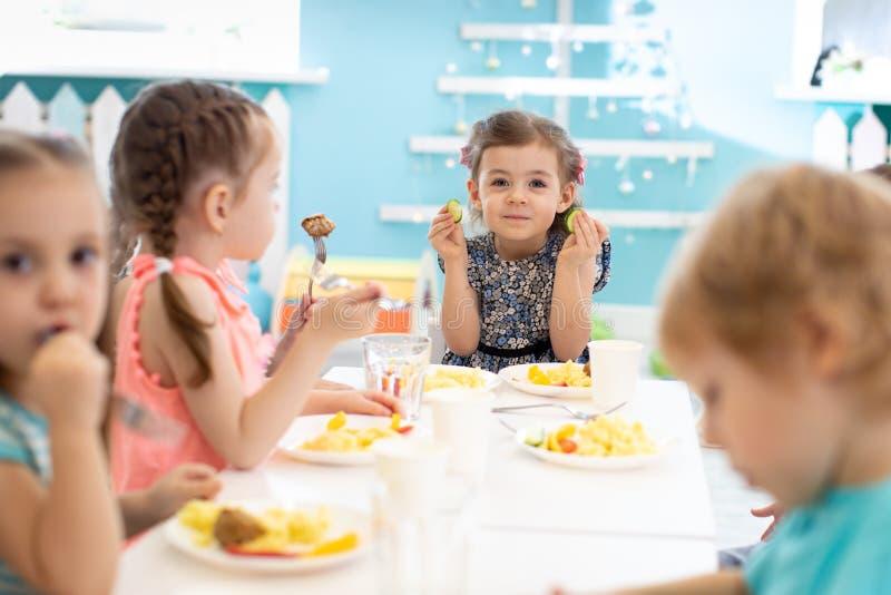 Group of kids eating healthy foo in kindergarten royalty free stock image
