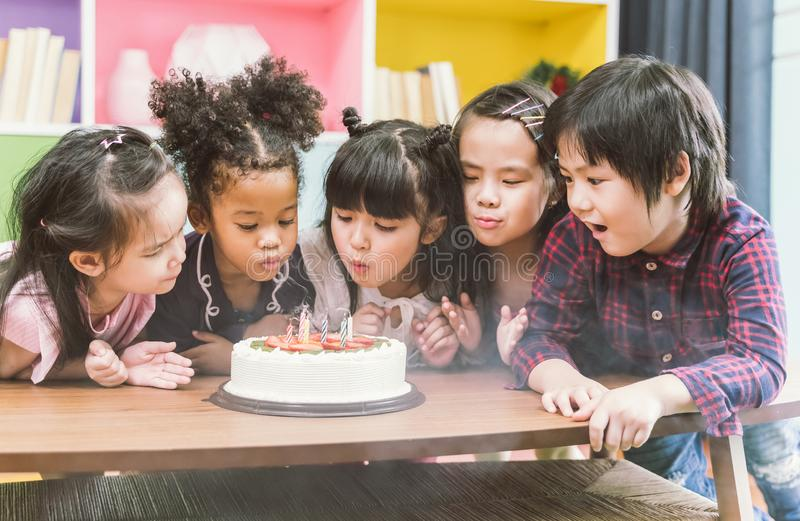 Group of kids enjoying a birthday party blowing out the candle on cake. stock photos