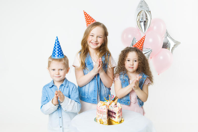 Group of kids in festive caps clap their hands near birthday cake, balloons on background royalty free stock photo