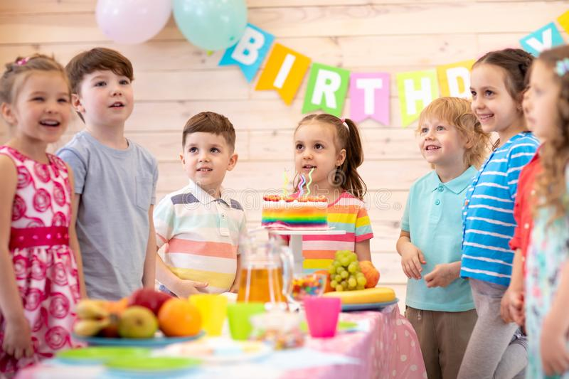 Group of kids having fun by festive table at birthday party stock photography