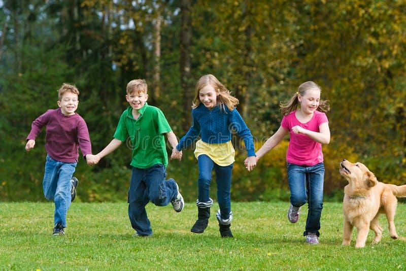 Group of kids having fun running royalty free stock photo