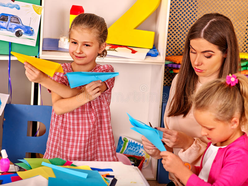 Group kids holding origami airplane in kindergarten . Woman with little girls playing origami paper airplane in kindergarten preschool royalty free stock photography