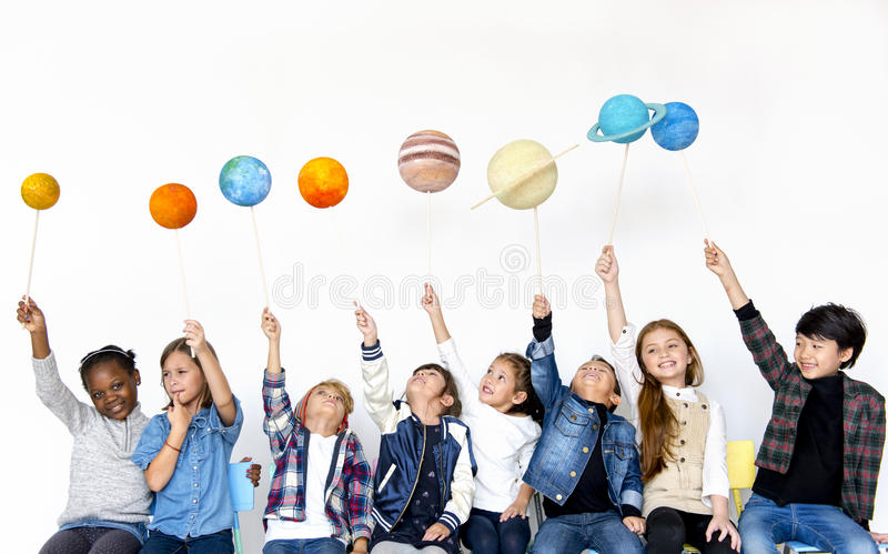 Group of Kids Holding Paper-craft Galaxy Symbol on White Background stock photo