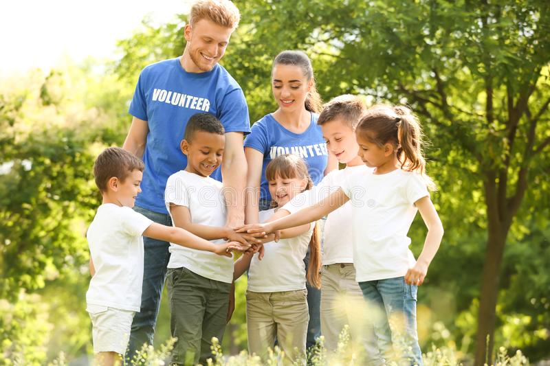 Group of kids joining hands with volunteers royalty free stock images