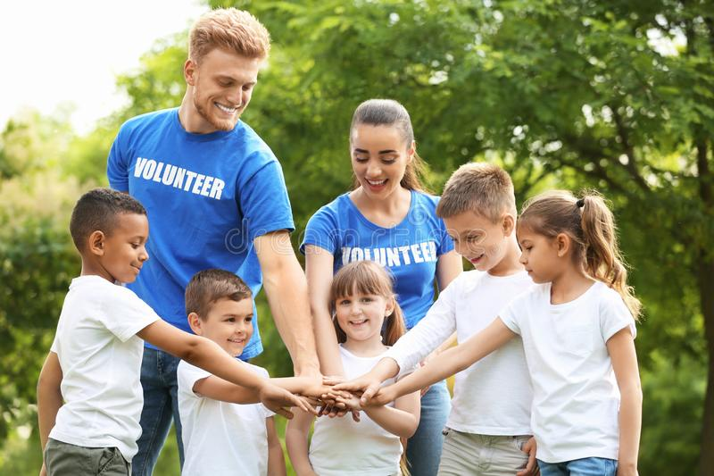 Group of kids joining hands with volunteers stock image