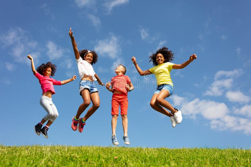 Group of kids jump high over blue sky and clouds royalty free stock image