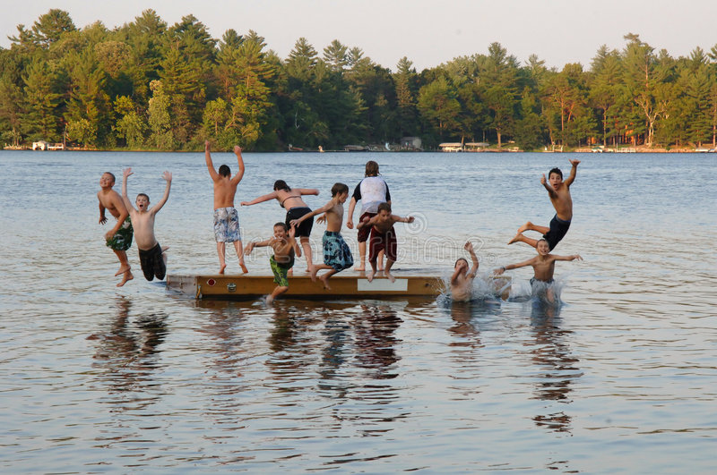 Group of kids jumping into Lake. A group of eleven kids ages 11-13 jumping off on a dock into a lake at sumer camp royalty free stock photos
