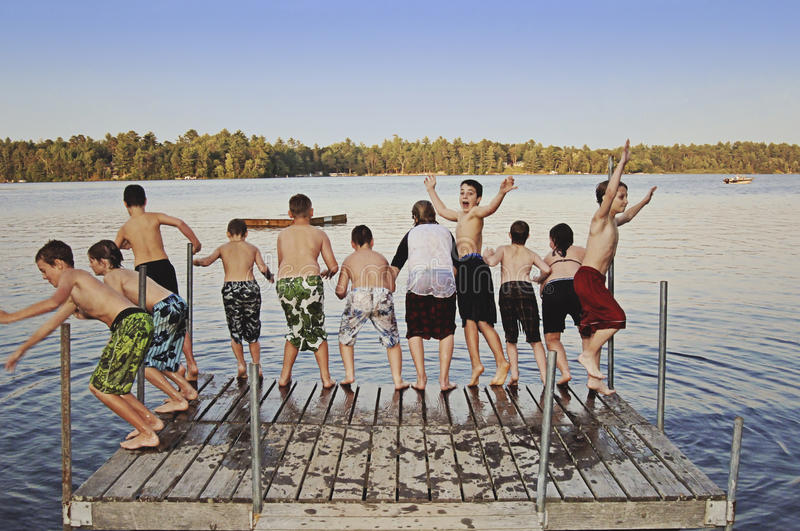 Group of kids jumping into Lake. A group of eight kids ages 11-13 jumping off on a dock into a lake at summer camp royalty free stock images