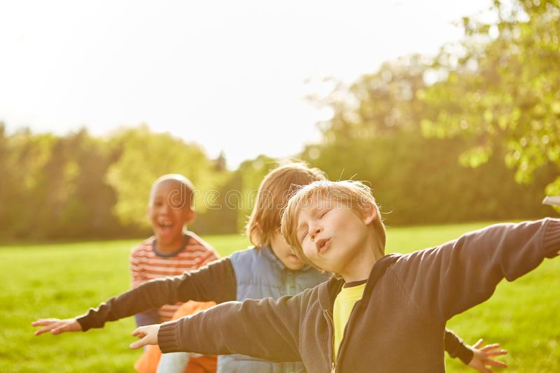 Group of kids in the park with outstretched arms stock photos