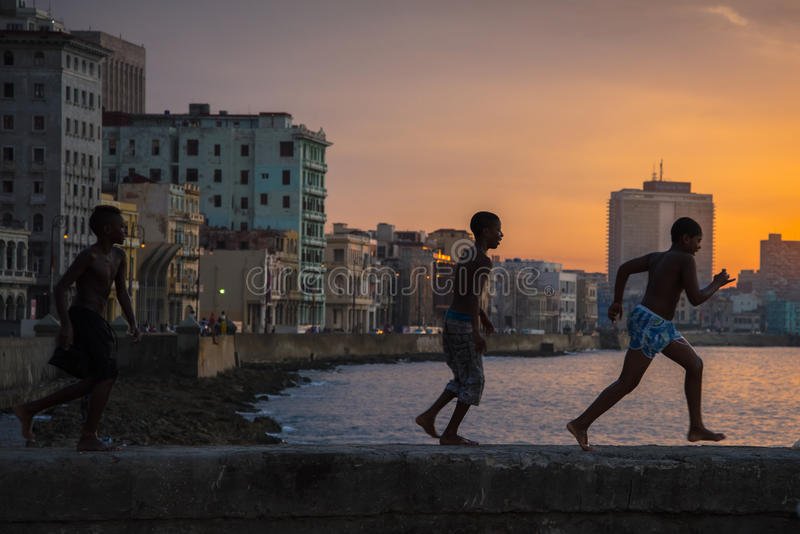 Group of kids play and jump from Malecon wall into Atlantic in H stock images
