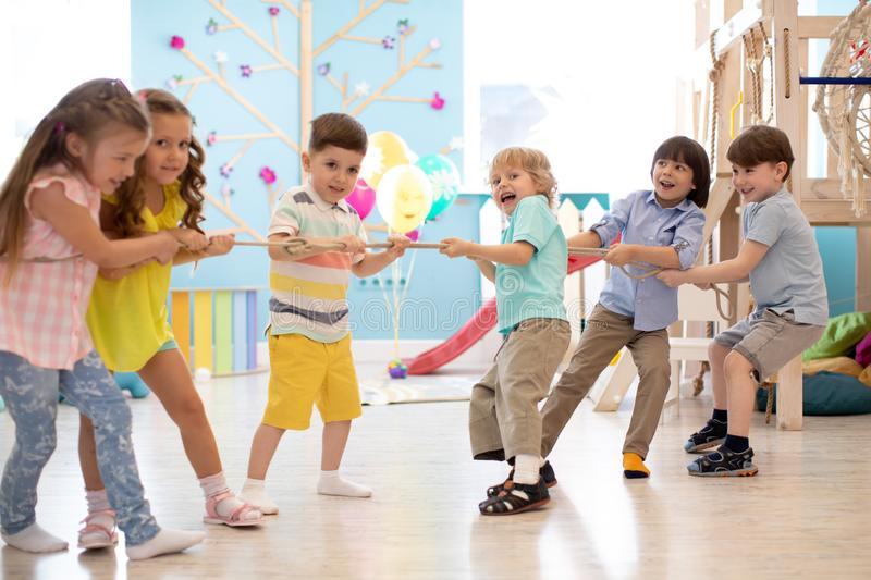 Group of kids play and pull rope together in daycare stock photo