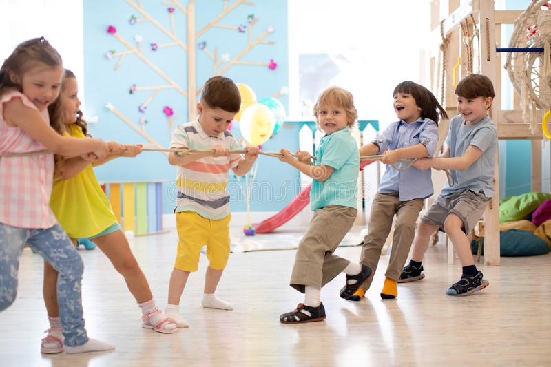 Group of kids play and pull rope together in daycare. Group of preschool kids play and pull rope together in daycare royalty free stock photography