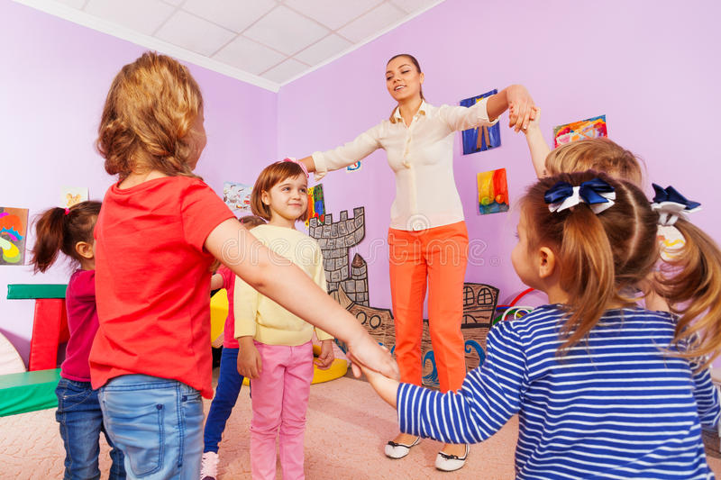 Group of kids play roundelay around girl royalty free stock photography