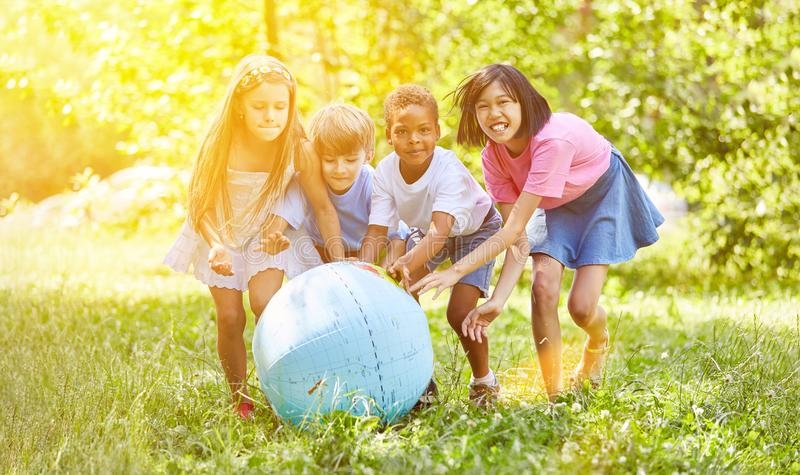 Group of kids while playing with world globe royalty free stock photography