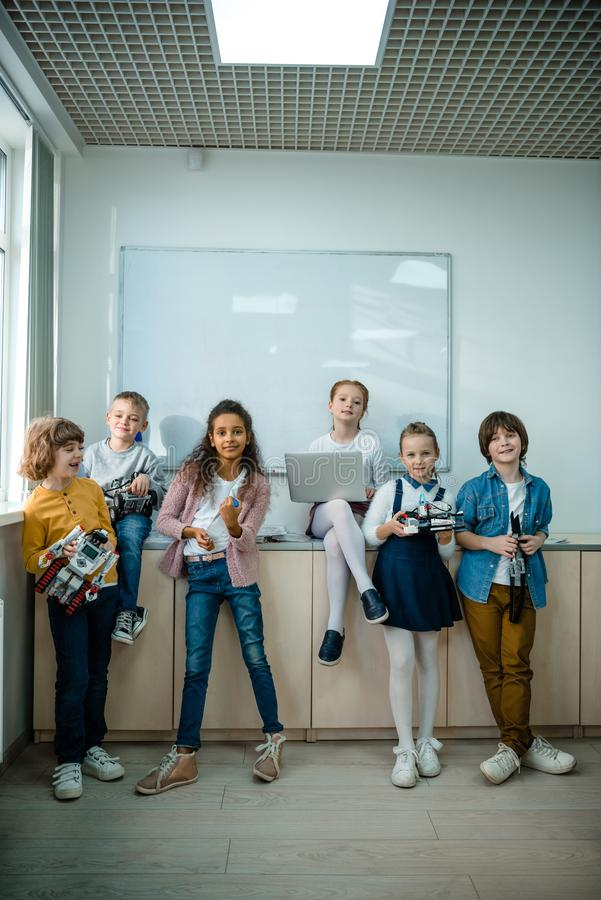 group of kids posing together with laptop and robots on stem stock images