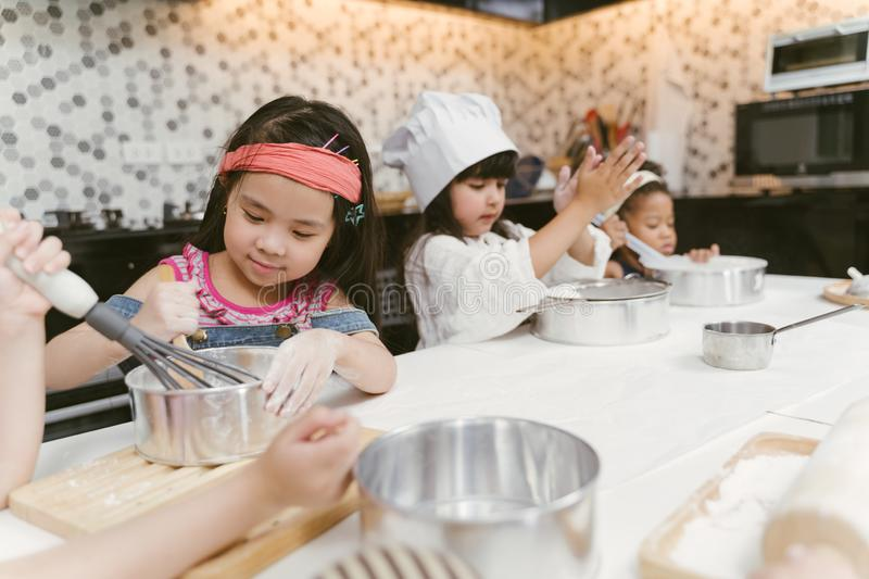 Group of kids are preparing the bakery in the kitchen .Children learning to cooking cookies. royalty free stock photo